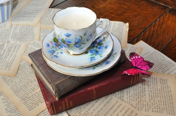Alice in Wonderland - vintage tea cup candles sits on top of old books and bespoke table runner